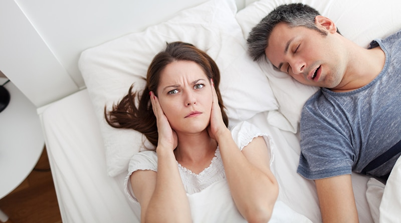 Woman covering ears, annoyed by husband's sleep apnea