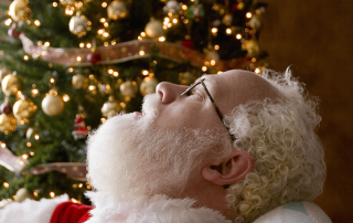 Santa Claus sitting by a Christmas Tree snoring after a busy night of delivering gifts