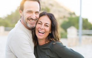 Happy older active couple spends time together outdoors on a sunny day without a care in the world. Recently they needed dental implants to complete their missing smiles. If you're considering dental implants in Rochester, NY, we can help.