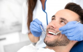 A young man sitting in a dental chair, showing off his smile. With a Holistic Dentist like the staff at Contemporary Dentistry we can help Rochester NY patients who have metal allergies.