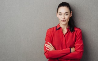 skeptical woman leans against a wall while while her arms are crossed, thinking