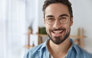 man with over sized glasses shows off his pearly whites