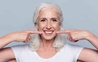 mature woman points to her big, wide smile