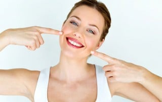 Beautiful woman points to her amazing healthy, smile